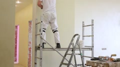 Worker is standing on scaffold and fixing the wall Stock Footage