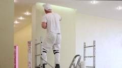 Worker is fixing the wall near ceiling using pallet. Stock Footage