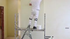 Builder is standing on scaffold and fixing the wall Stock Footage