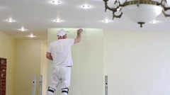 Worker is fixing the yellow wall near ceiling using pallet. Stock Footage