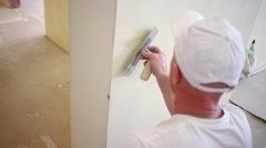 Plasterer in white cap evens stucco a wall using the pallet. - stock footage