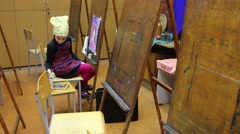 Girl in scarf and apron painting colorful picture at art class. - stock footage
