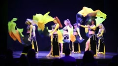 Women in black and yellow dresses  with fans dance in art cafe Stock Footage