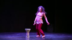 Young curly-haired woman in eastern suit finishes dance on stage. Stock Footage
