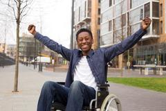Happy wheelchair user celebrating a success. Stock Photos