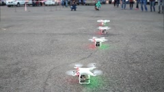 Four quadrocopters with rotating propellers stand in line Stock Footage