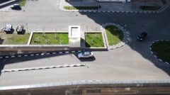 Two cars drive out of courtyard by marked paths, top view. Stock Footage