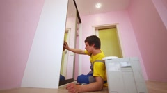 Worker sits on one side against wardrobe and checks mounted door. Stock Footage