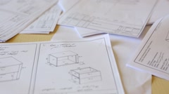Sheets of paper with drawings lie on the floor in room. Stock Footage