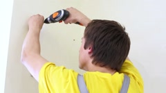 Worker mount brackets to the wall using electrical screwdriver. Stock Footage