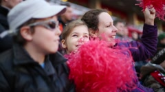 Happy mother, daughter and son with red pompoms look football - stock footage