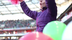 Woman in black cap shouts with red pompoms during football match Stock Footage