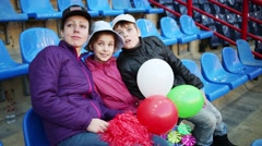 Mother, daughter and son with balloons sit on seats at stadium Stock Footage