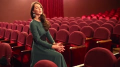 Beautiful woman in dress sits in empty red auditorium in theatre - stock footage