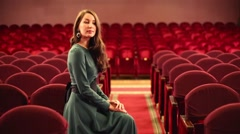 Back of woman going among seats in empty auditorium in theatre Stock Footage