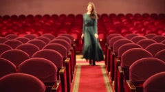 Woman goes among seats in empty red auditorium in theatre Stock Footage