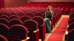 Beautiful woman in dress sits in empty auditorium in theatre Stock Footage