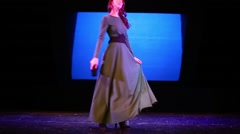 Beautiful woman dances on stage in empty auditorium of theatre Stock Footage