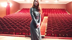 Beautiful woman in dress on stage in empty auditorium of theatre Stock Footage