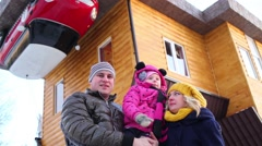 Family of three wave hands near roof of real inverted house Stock Footage