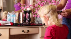 Back of little girl and hands of hairdresser with curling iron Stock Footage