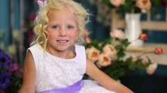 Little girl in dress sits on white fur and smiles among flowers Stock Footage