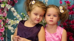 Little girls in dresses look at camera and smile in room Stock Footage