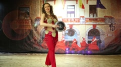 Woman in red costume dances belly dance with small drum Stock Footage