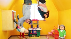 Family of four in children room upside down at inverted house Stock Footage