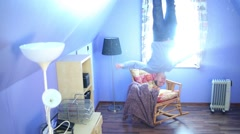 Man jumps on ceiling above armchair upside down at inverted house Stock Footage
