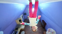 Little girl and boy walk on ceiling upside down at inverted house Stock Footage