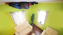 Man lies on ceiling above sofa without shoes in inverted house Stock Footage