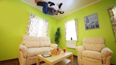 Man sleeps on ceiling above sofa without shoes in inverted house Stock Footage