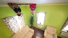 Two children upside down sit on ceiling in room of inverted house Stock Footage