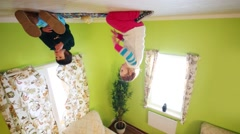 Boy and girl upside down sit on ceiling and eat in inverted house Stock Footage