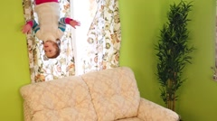 Little girl touches sofa upside down in room of inverted house Stock Footage