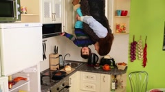 Woman with son upside down in kitchen at inverted house Stock Footage