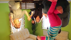 Family sits on ceiling upside down with candles at inverted house Stock Footage