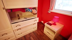 Little girl lies upside down in closet at inverted house Stock Footage