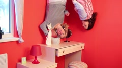 Two women upside down in bedroom above dressing table Stock Footage