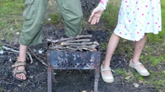 Brazier on lawn and children hands laying dry twigs for firing Stock Footage
