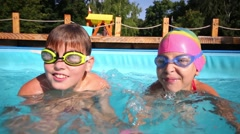 Boy and girl in swimming goggles dives in pool at summer day Stock Footage