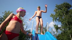 Boy on slide and girl in swimming goggles dance and dive into pool Stock Footage