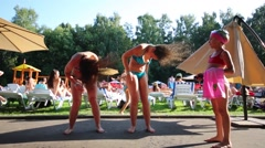 Two women shake hair and girl stands next to them and swimming pool Stock Footage