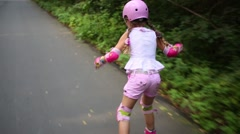 Back of girl in pink helmet riding on roller skates in park Stock Footage