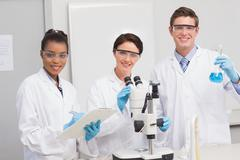 Scientists working attentively with microscope and beaker Stock Photos