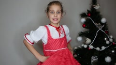 Smiling girl dressed in white blouse and red pinafore dress dances Stock Footage