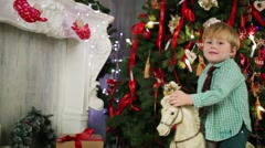 Little boy sits on rocking horse in room near christmas tree Stock Footage