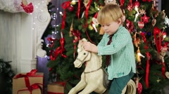 Little boy sits on rocking horse near decorated christmas tree Stock Footage