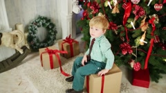 Little cute boy sits on gift box near decorated christmas tree Stock Footage